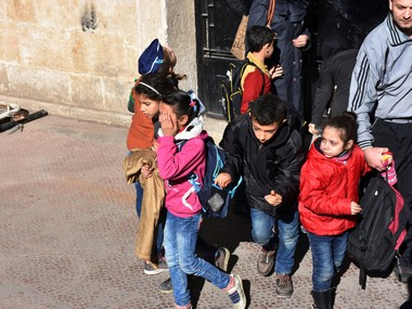 Schoolchildren react as they evacuate a school after shelling by Syrian rebels on government-held western Aleppo, Syria in this handout picture provided by SANA on 20 November. Reuters