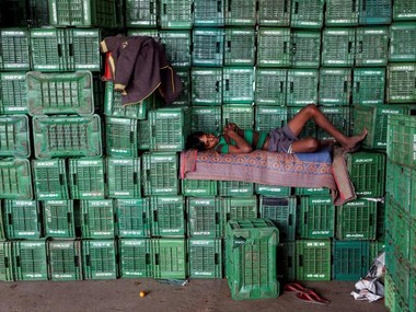 A labourer sleeps on baskets of unsold tomatoes at a wholesale market in Manchar village in the western state of Maharashtra, India. Reuters