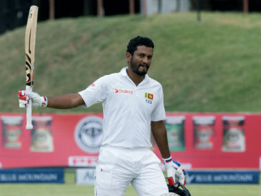 Dimuth Karunaratne raises his bat after completing his century. AFP