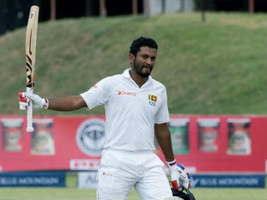 Dimuth Karunaratne raises his bat after completing his century. AFP