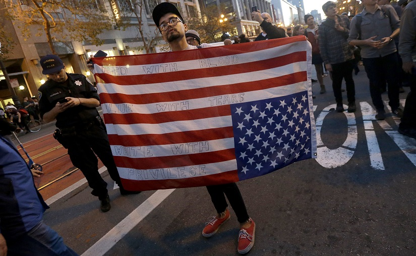 A protester carries an upside down American flag in opposition of Donald Trump's presidential election victory in San Francisco on Wednesday. AP