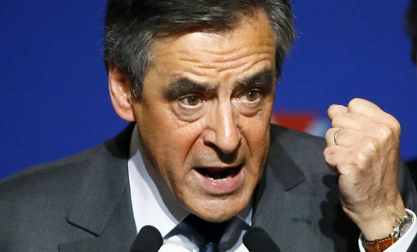 Francois Fillon, a candidate in Sunday's primary runoff to select a conservative candidate for the French presidential election, delivers his speech during a rally in Paris, Friday, Nov. 25, 2016. Fillon, a champion of free-market economics and traditional family values must defeat Alain Juppe a moderate who accuses his rival of pandering to the far right. Woman at right is unidentified. (AP Photo/Francois Mori)