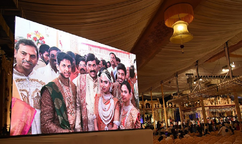 Indian mining tycoon, Gali Janardhan Reddy, (C) is seen on a big screen as he poses with his daughter Bramhani (2R) and son-in-law, Rajeev Reddy (2L) during their wedding in Bengaluru. Getty Images.