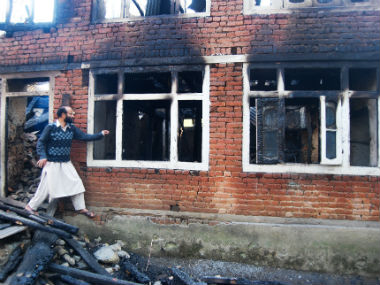 Dildar Ahmad Bhat stands next to a class room of Iqra Public School which was burnt. Sameer Yasir/Firstpost