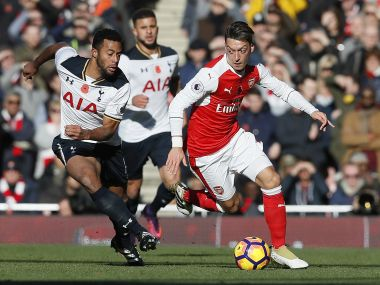 Arsenal's Mesut Ozil, right, vies for the ball with Tottenham's Mousa Dembele. AP