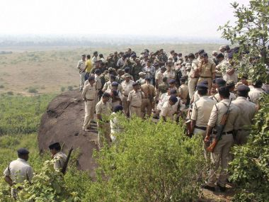 Police investigate the encounter site at the hillocks of Acharpura village after the STF killed 8 SIMI activists. PTI