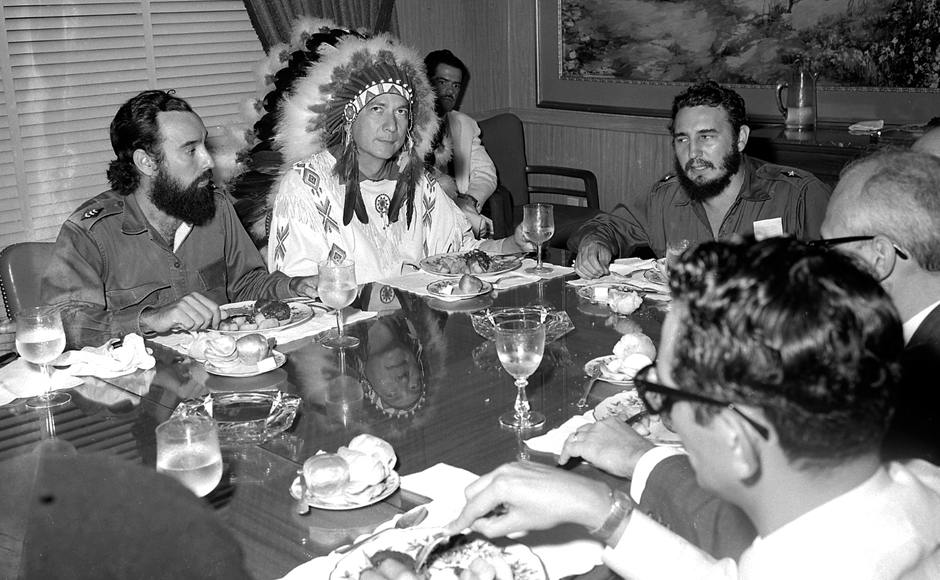"""Fidel Castro (R) meets with Reverend WA Raifford (2nd-L), chief of the White Birds from the Creek Indians in Havana, 16 July, 1959. Raifford gave Castro the name Spiheechie Meeko (Big Warrior Chief). The bearded, cigar-puffing leader, renowned for trademark army fatigues and hours-long public tirades, grabbed power in a January 1, 1959 revolution. Living by the slogan """"socialism or death,"""" Castro kept the faith to the end, even as the Cold War came and went."""