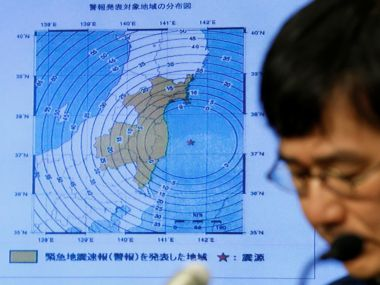A news conference next to the map showing an earthquake epicentre off the coast of Fukushima prefecture. Reuters