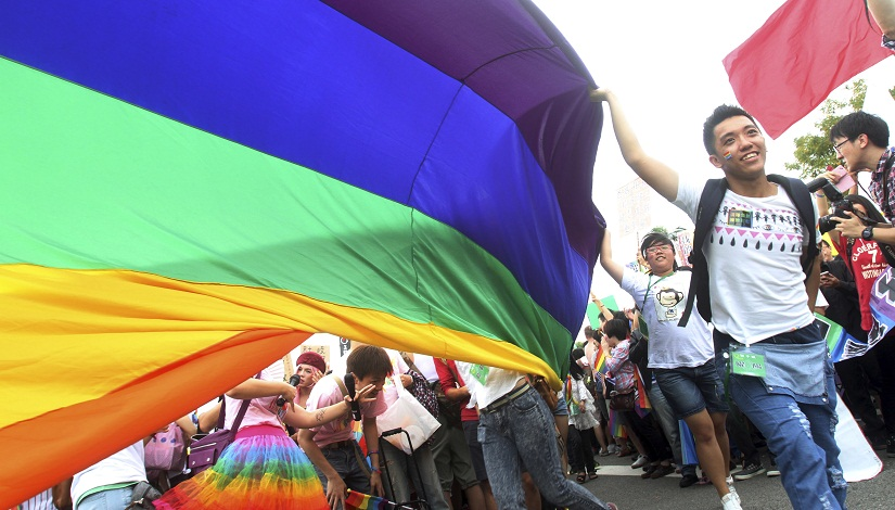 FILE - In this Saturday, Oct. 25, 2014, file photo, participants revel through a street during a gay and lesbian parade in Taipei, Taiwan. Thousands of gay and lesbian Taiwanese took to the streets showing Taiwan's acceptance of alternative lifestyles and activities from traditional ways of Chinese life. (AP Photo/Chiang Ying-ying, File)