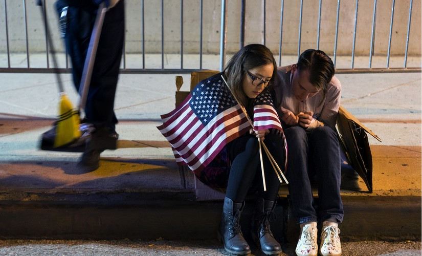 People sit outside the Jacob Javits Center waiting for election results following a rally for Democratic presidential candidate Hillary Clinton in New York. AP