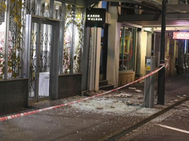 Glass and masonry litter the footpath in Wellington on Monday. AP