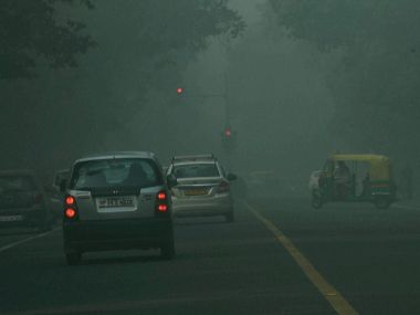 Vehicles on smog covered road in New Delhi. PTI