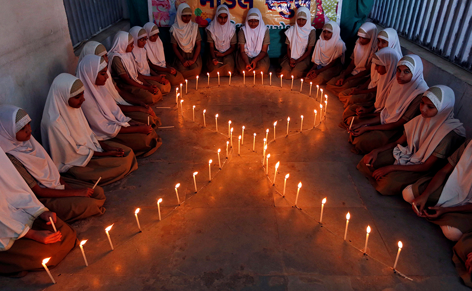 School girls light candles in the shape of a ribbon during a HIV/AIDS awareness campaign ahead of World Aids Day, in Ahmedabad, India November 30, 2016. REUTERS