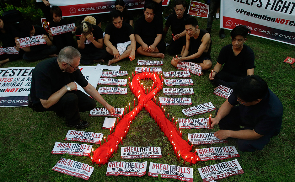 A priest lights candles around an AIDS symbol as he participates in an event in observance ofWorld AIDS Day in Quezon city, Philippines on Thursday, Dec. 1, 2016. The group is calling for increased awareness to the rising number of HIV infections and AIDS-related cases and called on the government and other sectors to help break the social stigma brought about by the disease. (AP Photo/Aaron Favila)