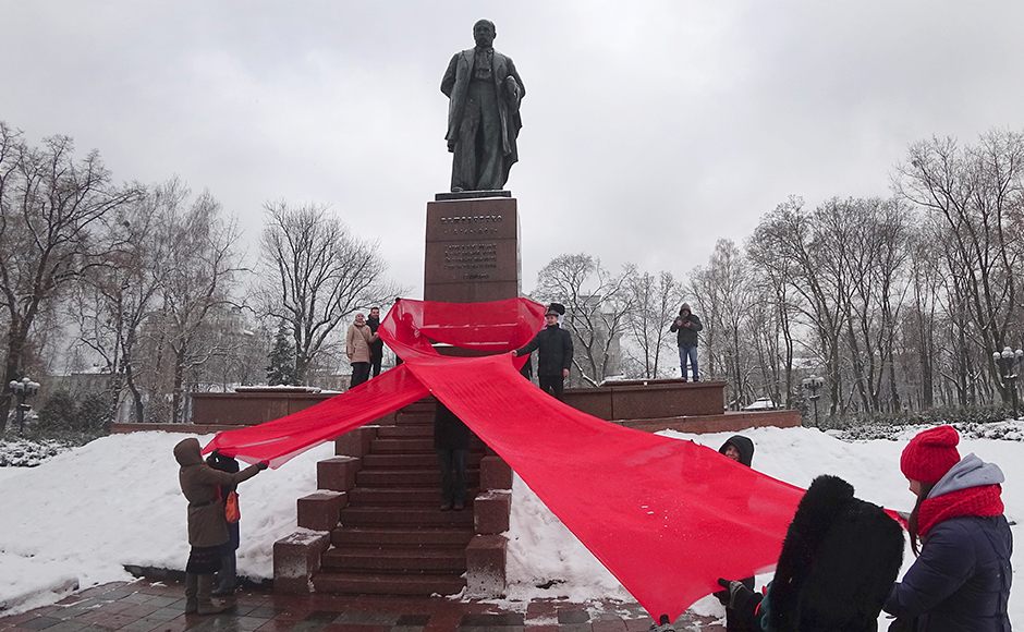 Activists hold huge red ribbon in front of the monument to Taras Shevchenko, famous Ukrainian poet to mark the 'World AIDS Day' and in memory of those who have died of AIDS in Kiev, Ukraine, Thursday, Dec. 1, 2016. (AP Photo/Efrem Lukatsky)