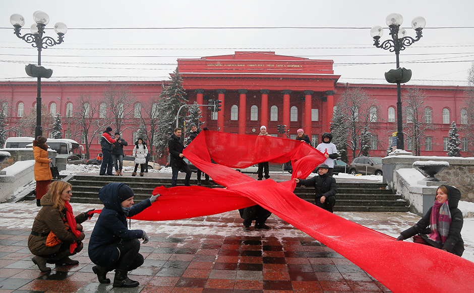 Activists hold huge red ribbon in front of the Taras Shevchenko National University Kiev, Ukraine, to mark the 'WorldAIDSDay' and in memory of those who have died of AIDS Thursday, Dec. 1, 2016. (AP Photo/Efrem Lukatsky)