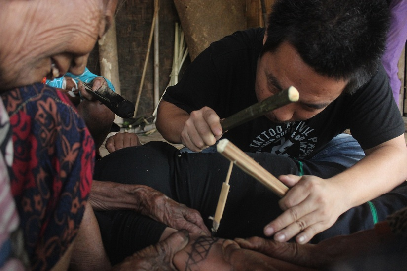 One of the last tattooing queens of Konyak teaching Mo Naga the art of traditional tattooing