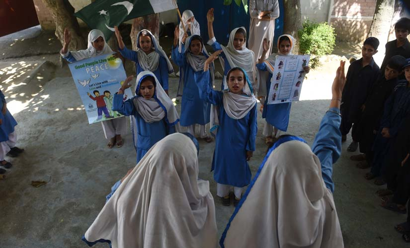 In this photograph taken on August 30, 2016, Hindko speaking schoolchildren sing the national anthem at their school in Mansehra. Around a hundred women have gathered in a community centre in Peshawar, the heart of Pakistan's fabled northwest — but they are conversing in a dialect incomprehensible to the Pashtun ethnic group that dominates the region. AFP