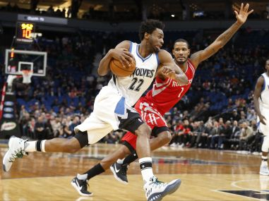 Minnesota Timberwolves' Andrew Wiggins races by as Houston Rockets' Trevor Ariza pursues. AP