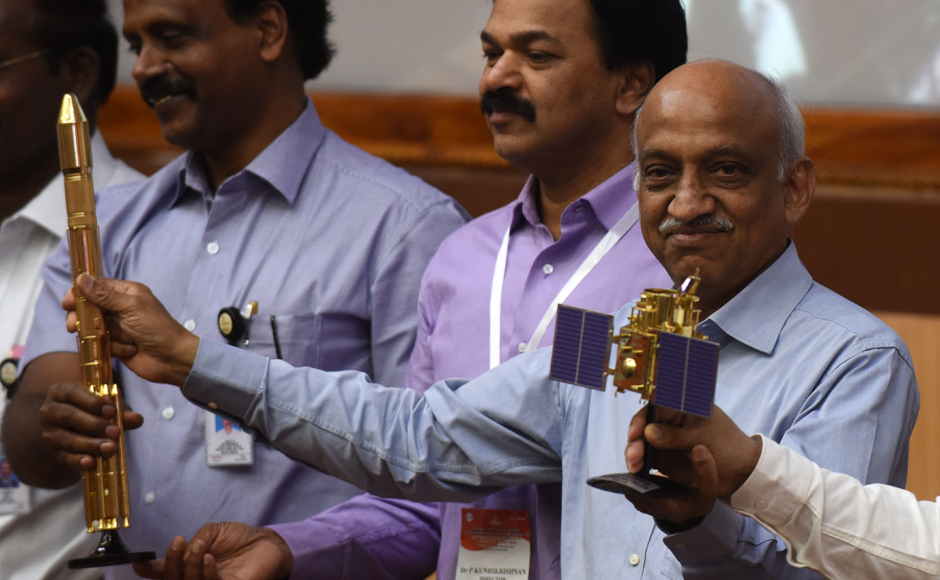 Indian Space Research Organisation (ISRO) chairman Kiran Kumar Rao (R) displays models of the CARTOSAT-2 and Polar Satellite Launch Vehicle (PSLV-C37) as he speaks to media after the launch of the Polar Satellite Launch Vehicle (PSLV-C37) at Sriharikota on Febuary 15, 2017. India successfully put a record 104 satellites from a single rocket into orbit on February 15 in the latest triumph for its famously frugal space agency. Scientists who were at the launch in the southern spaceport of Sriharikota burst into applause as the head of India's Space Research Organisation (ISRO) announced all the satellites had been ejected. ARUN SANKAR / AFP