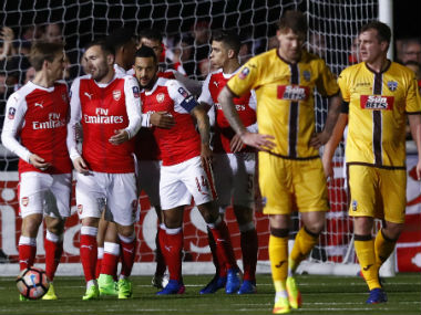 Arsenal players celebrate Theo Walcott's goal, his 100th for the London-based club. Reuters