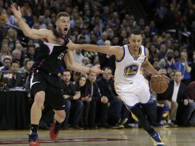 Golden State Warriors' Stephen Curry, right, drives past Los Angeles Clippers' Blake Griffin. AP
