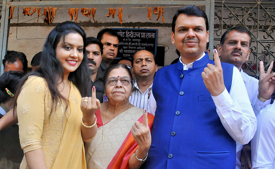 Maharashtra chief minister Devendra Fadnavis along with mother (C) and wife Amruta (R) showing ink marked fingures after cast their votes during the Municipal election in Nagpur of Maharashtra on Tuesday. PTI Photo(PTI2_21_2017_000105B)