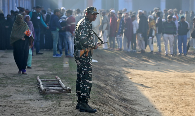 A soldier stands guard as people queue to cast their vote during the state assembly election, in the village of Kairana, in the state of Uttar Pradesh, India, February 11, 2017. REUTERS/Cathal McNaughton - RTSY5A4
