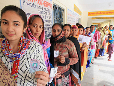 Voters lined up at a polling booth in Punjab. PTI.