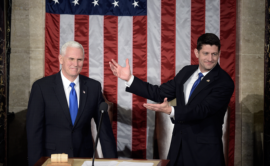 US Vice President Mike Pence (L) is welcomed by House Speaker Paul Ryan before US President Donald Trump addresses a joint session of the US Congress on February 28, 2017, in Washington, DC. Brendan SMIALOWSKI / AFP