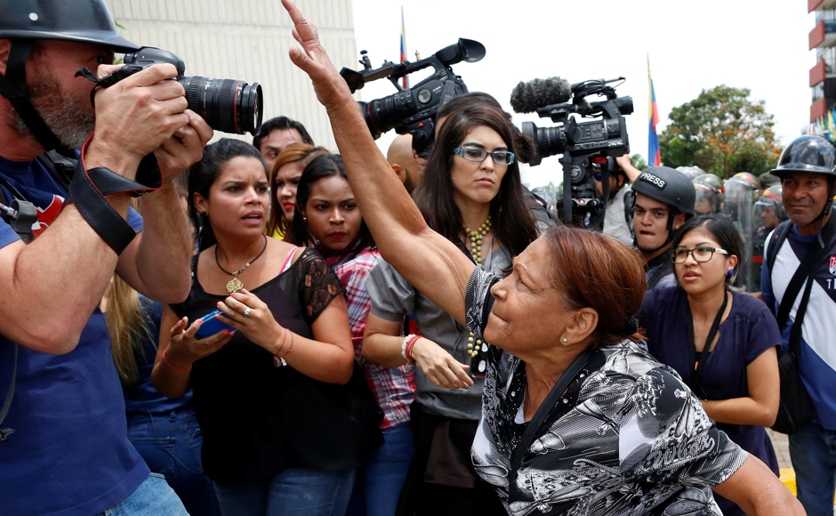 A supporter of Venezuela's President Nicolas Maduro tries to take the camera of a photographer away, during clashes with opposition supporters outside the Supreme Court of Justice (TSJ) in Caracas. REUTERS/Carlos Garcia Rawlins
