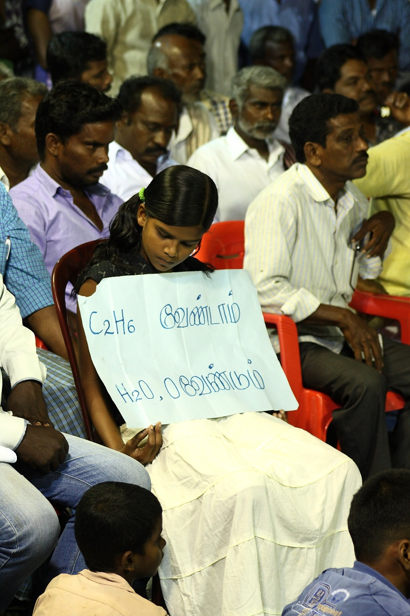 A girl protesting in Neduvasal, holds a placard that says 'We Don't Want Methane; We Want Water and Oxygen'