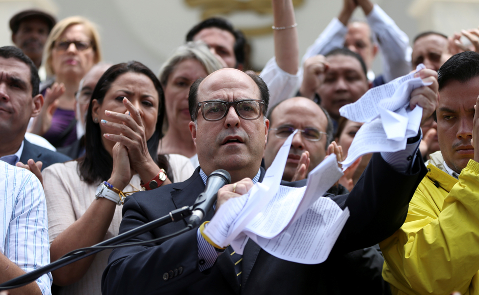 Julio Borges (C), President of the National Assembly and deputy of the Venezuelan coalition of opposition parties (MUD), tears a copy of a sentence of the Venezuela's Supreme Court during a news conference in Caracas. REUTERS/Carlos Garcia Rawlins