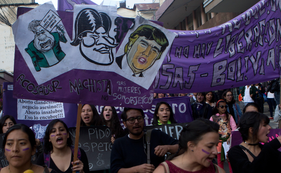 "A woman carries a sign showing images of U.S. President Donald Trump, top right, and Bolivia's President Evo Morales, center, over the Spanish words: ""Macho stalker"" during a protest against violence against women in La Paz, Bolivia, Wednesday, March 8, 2017. Women around the world are marching to commemorate International Women's Day. (AP Photo/Juan Karita)"