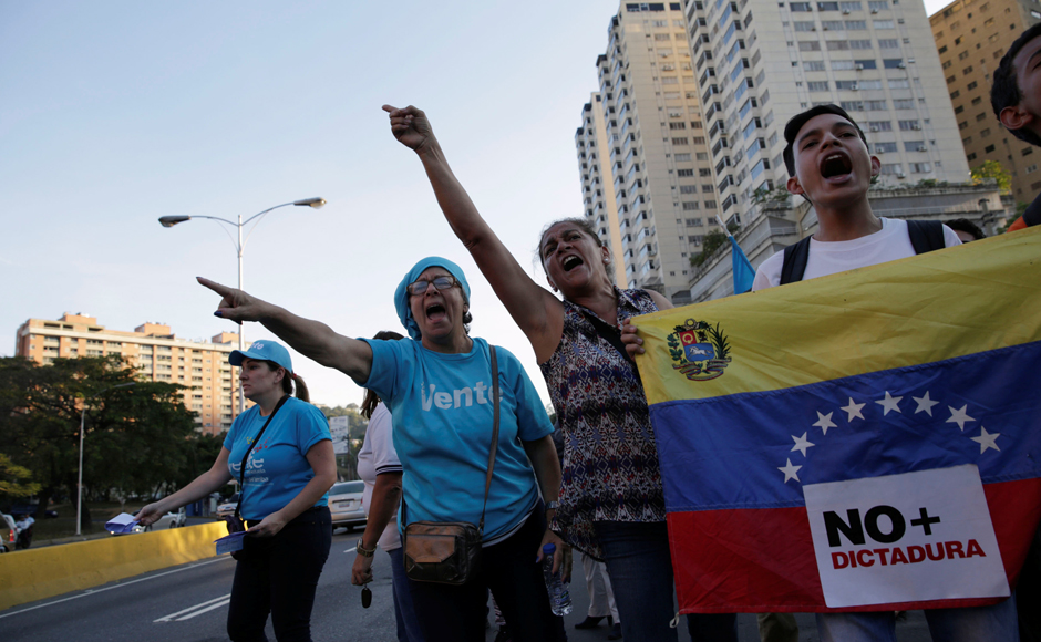 Opposition supporters shout slogans as they block a highway during a protest against Venezuelan President Nicolas Maduro's government, in Caracas. REUTERS/Marco Bello