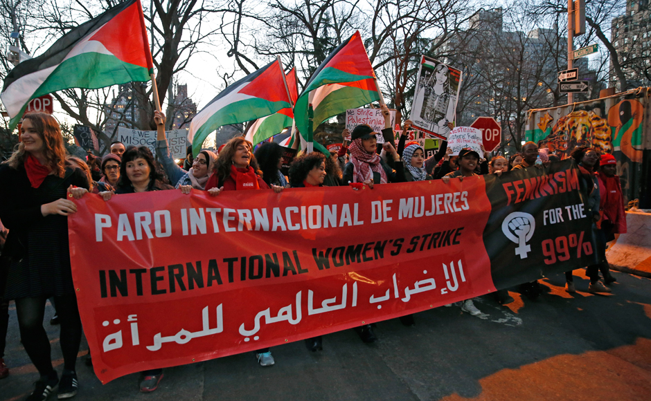 Women hold a banner along with others waving Palestinian flags as they gathered at the edge of Washington Square park before marching following a rally organized by International Women's Strike NYC, a coalition of dozens of grassroots groups and labor organizations, Wednesday, March 8, 2017, in New York. (AP Photo/Kathy Willens)