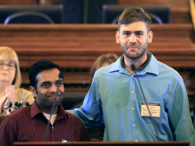 Alok Madasani, left, and Ian Grillot, right, embrace and smile after they were honored by the Kansas House of Representatives in Topeka, Kansas.Thursday, March 16