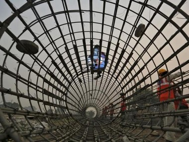 Labourers work at the construction site of a bridge being built for metro rail in New Delhi. Reuters