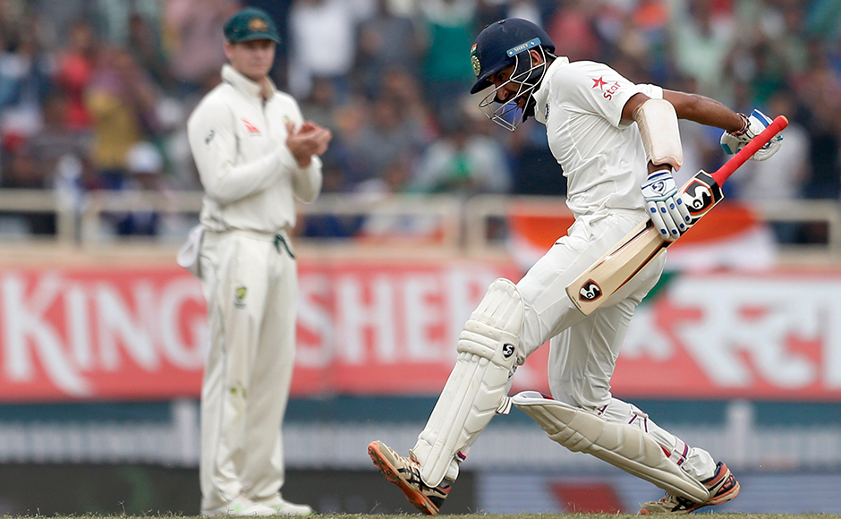 Australia's captain Steven Smith, left, applauds as India's Cheteshwar Pujara celebrates scoring a double hundred during the fourth day of their third test cricket match in Ranchi, India, Sunday, March 19, 2017. (AP Photo/Aijaz Rahi)