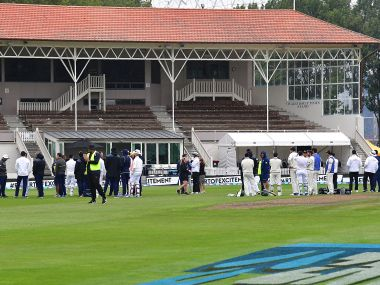 New Zealand and South Africa players and officials stand in the middle of the field after a fire alarm on day three of the first Test. AFP