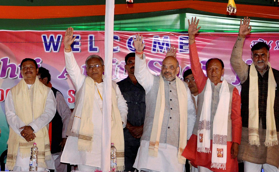 BJP President Amit Shah with party members waves at crowd at an election rally at Singjamei in Manipur on Wednesday. PTI Photo (PTI3_1_2017_000169B)