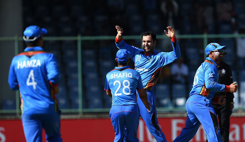 Afghanistan's Mohammad Nabi(C)celebrates the wicket of England's captain Eoin Morgan during the World T20. AFP