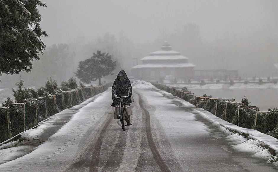 A Kashmiri milkman cycles on a snow covered road on the outskirts of Srinagar, Indian controlled Kashmir, Thursday, April 6, 2017. Heavy snowfall and rains have forced authorities in Indian controlled Kashmir to close schools and colleges even as the only all weather road link that connects the Kashmir valley to the rest of India has been cut off. (AP Photo/Dar Yasin)