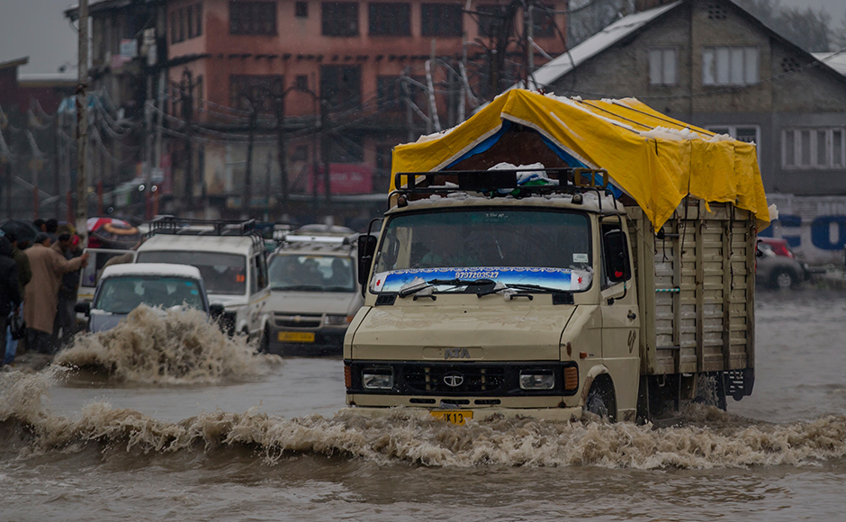 Vehicles navigate their way through a waterlogged street in Srinagar, Indian controlled Kashmir, Thursday, April 6, 2017. Heavy snowfall and rains have forced authorities in Indian controlled Kashmir to close schools and colleges even as the only all weather road link that connects the Kashmir valley to the rest of India has been cut off. (AP Photo/Dar Yasin)