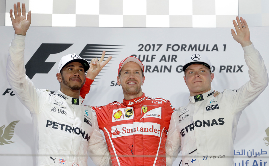Ferrari driver Sebastian Vettel of Germany, center, celebrates after winning the Bahrain Formula One Grand Prix, with second placed Mercedes driver Lewis Hamilton of Britain, left and Mercedes driver Valtteri Bottas of Finland, right, at the Formula One Bahrain International Circuit in Sakhir, Bahrain, Sunday, April 16, 2017. (AP Photo/Luca Bruno)