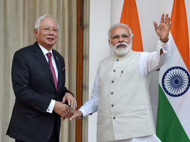 Prime Minister Narendra Modi shake hands with  his Malaysian counterpart Najib Razak and waves to a gathering, before their meeting at Hyderabad House in New Delhi on Saturday. PTI