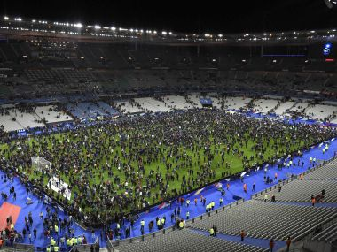 Spectators gather on the pitch of the Stade de France Stadium after a series of explosions outside the stadium. AFP