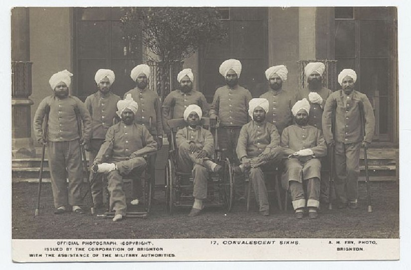This monochrome photographic postcard was produced during World War One, when the Royal Pavilion was used as a military hospital for wounded Indian soldiers. It shows a group portrait of twelve 'Punjaubi Mahommedans'. This term was used by the British to describe Muslims from the Punjab region of India. This postcard was part of a series of views of the Pavilion Military Hospital which were produced by the Brighton Corporation and the military authorities. This image is one of several which show the 'martial races' that fought for the British and were cared for at the Royal Pavilion. Wikimedia Commons