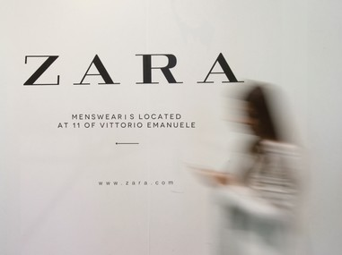 A woman walks in front of an advertisement for an Inditex owned Zara store in Milan, Italy, March 30, 2017. REUTERS/Alessandro Garofalo - RTX340DU