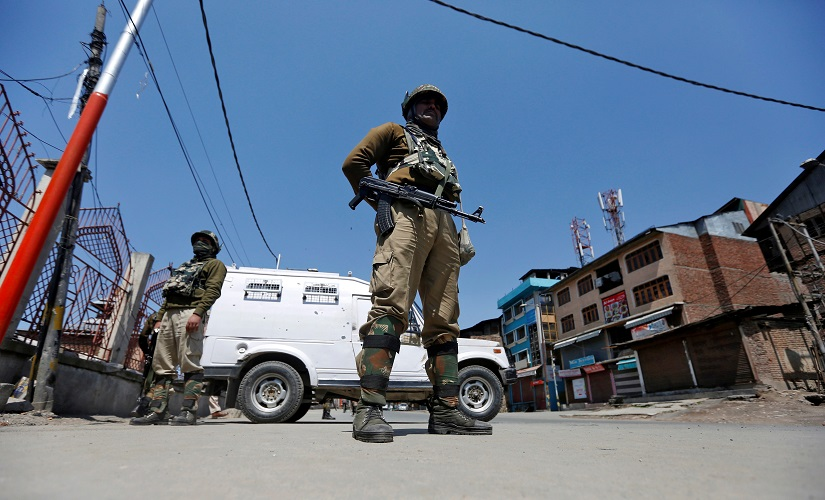 Security forces in Kashmir guard a deserted street during restrictions in downtown Srinagar. Reuters